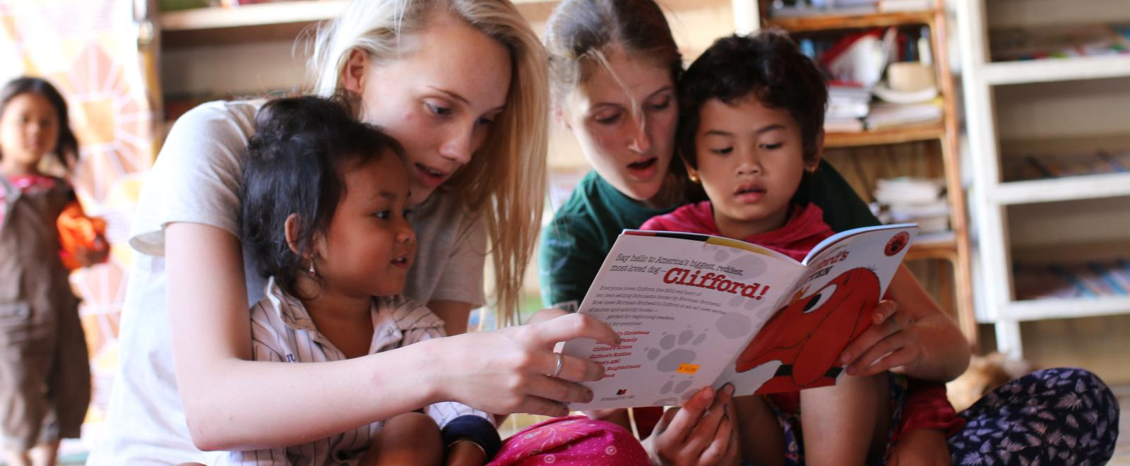 Childcare volunteers read a book to the children at a day care centre in Cambodia